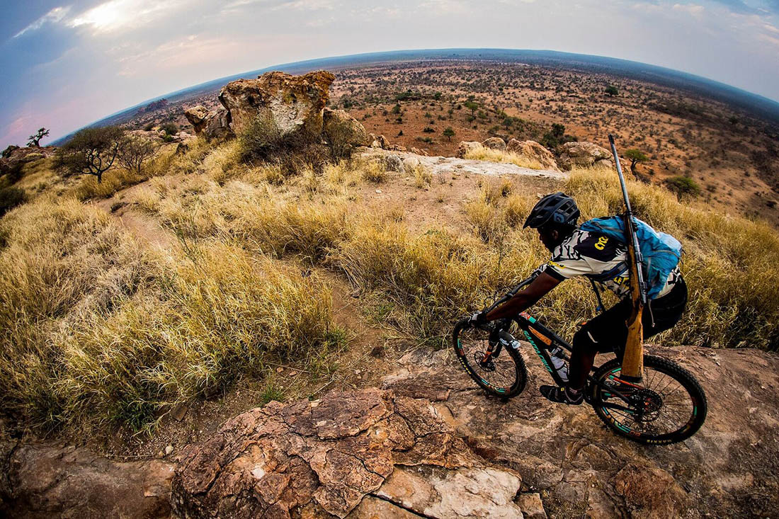 Juliana Bicycles - Mosa Riding with Rifle in Africa